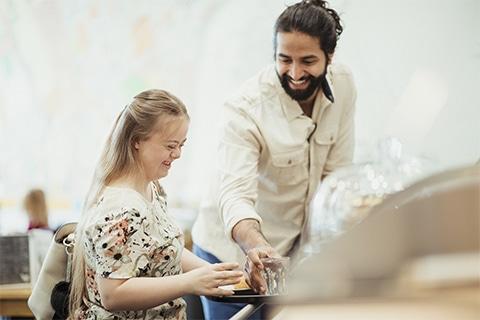 Einem jungen Mädchen mit Downsyndrom wird von einem jungen Mann ein Glas Wasser gereicht. Beide lächeln