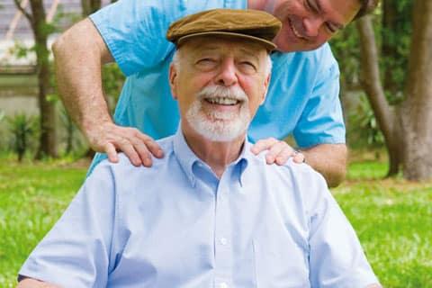 Alter Mann im wird von einem Pfleger draußen im Grünen massiert. Der Mann sitzt