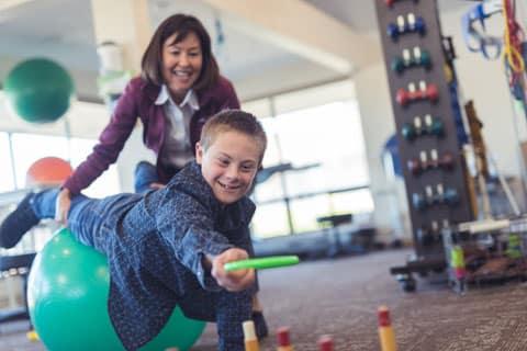 Junge mit Downsyndrom auf einem Gymnastikball. Im Hintergrund weitere Sportgeräte