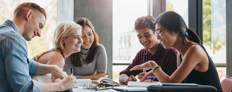 5 junge Leute Leute an einem Tisch mit Lernunterlagen