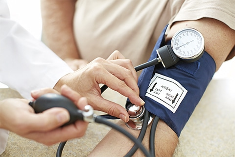 Arm mit Blutdruckmessgerät. Ärztin untersucht
