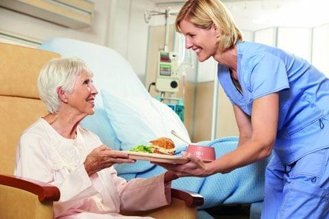 Einer älteren Frau in einem Krankenzimmer, wird von einer Pflegerin ein Tablett mit essen gereicht. Beide lächeln sich an
