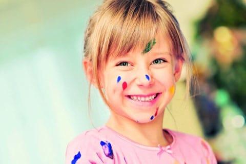 Lachendes Mädchen mit Farbtupfern im Gesicht. Trägt ein Rosafarbenes T-Shirt